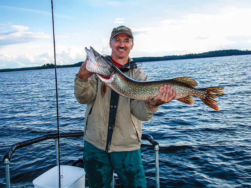 man in boat holding pike