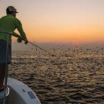 Man on boat fishing for false albacore
